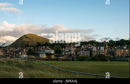 View from shore across the putting green to Berwick Law, North Berwick, East Lothian, Scotland, UK, in evening light - Stock Photo