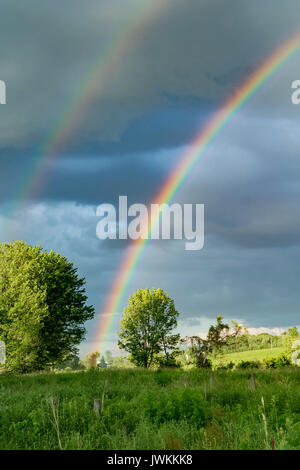 A beautiful rainbow over a farm field in New York. - Stock Photo