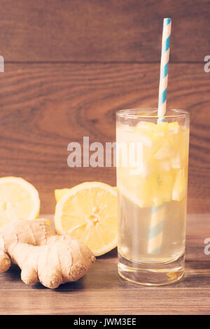 Ginger ale with lemon to accelerate metabolism. Refreshing healthful beverage. Wooden background. Vintage tinted - Stock Photo