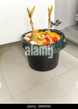 Separate garbage collection. Organic waste in the black bucket and plastic bag. - Stock Photo