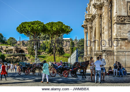Tourists at the Arch of Constantine near the Colosseum and the Roman Forum with Capitoline Hill in the background - Stock Photo