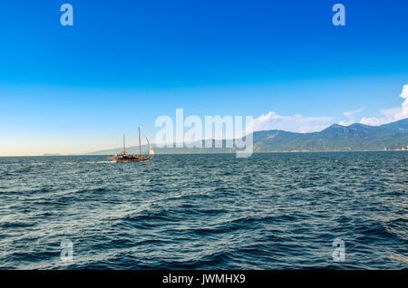 Yacht sailing in blue sea on sunset - Ionian Sea - Greece near Parga - Stock Photo
