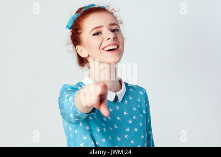 Funny redhead girl in light blue dress having, pointing finger at camera and toothy smile, focus on her face. Isolated - Stock Photo