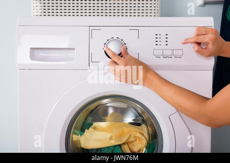 Close-up Of Person Hand Pressing Button Of Washing Machine For Laundry - Stock Photo