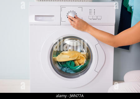 Close-up Of Person Hand Pressing Button Of Washing Machine For Clothes Laundry - Stock Photo