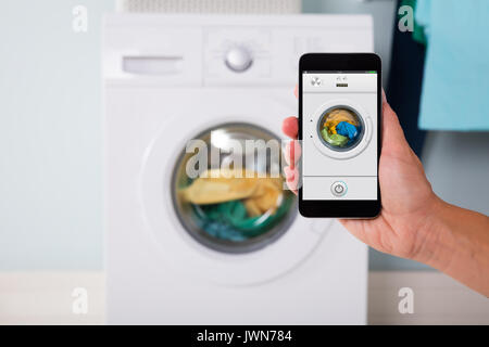 Close-up Of Person Hand Operating Smart Washing Machine Using Mobile Phone App - Stock Photo