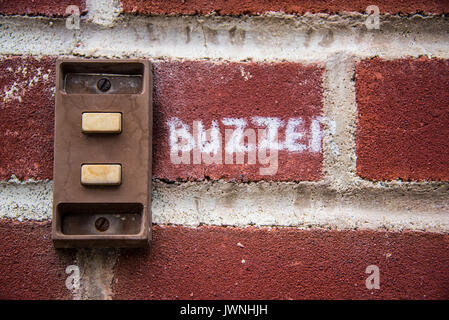 Old rusted metal buzzer on a brick wall with the handwritten word Buzzer painted on the bricks in white lettering - Stock Photo