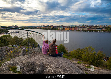 Tourists couple in Stockholm enjoying cityscapes of old town from rock - Stock Photo