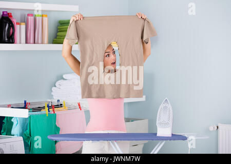 Shocked Woman Looking Through Burned Iron Cloth Standing Near The Ironing Board At Home - Stock Photo
