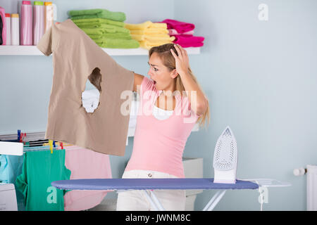 Young Shocked Woman With Burned Iron Cloth Standing Near The Ironing Board At Home - Stock Photo