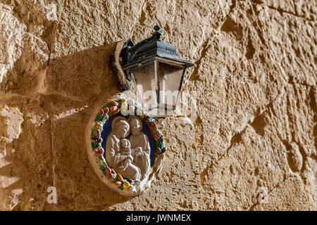 Virgin Mary and a child. Icon under a lantern on a texture wall of a house at the mediterranean island Malta. - Stock Photo