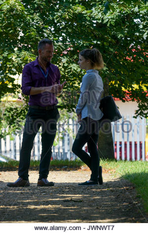 Man talking to younger woman, Poole, Dorset, England, UK - Stock Photo