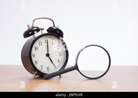 Old Fashioned Bell Alarm Clock And Magnifying Glass Standing On Edge On Top  Of A