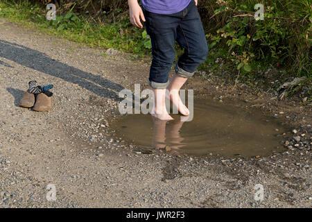boy walking barefoot through puddle - Stock Photo