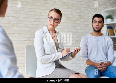 Portrait of beautiful female psychiatrist wearing glasses listening intently to patient during group therapy session, - Stock Photo