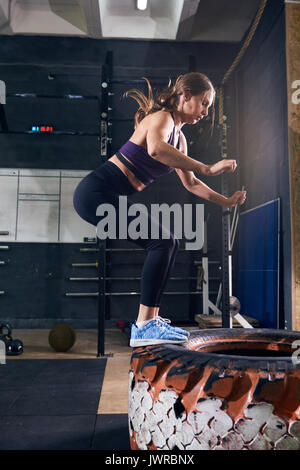 Side view portrait of strong young woman jumping on tire during crossfit workout in modern gym - Stock Photo