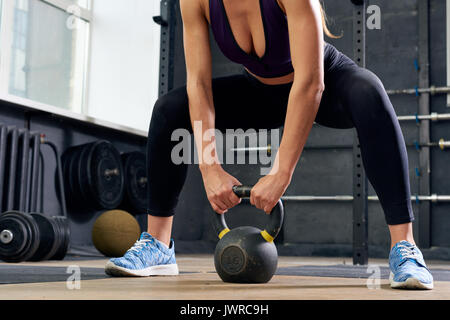 Low section portrait of unrecognizable young woman weightlifting, squatting with kettlebell during crossfit workout - Stock Photo