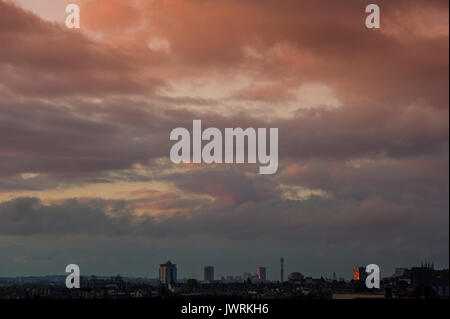 A setting sun reflects in a a tower block on the London skyline with the BT Tower - Stock Photo