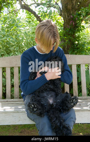 A blonde teenaged boy hugs his black dog - Stock Photo