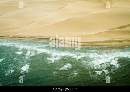 Atlantic Ocean meets Namib Desert waves and sand dunes horizonal - Stock Photo