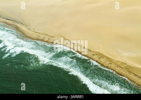 Atlantic Ocean meets Namib Desert waves and sand dunes diagonal - Stock Photo