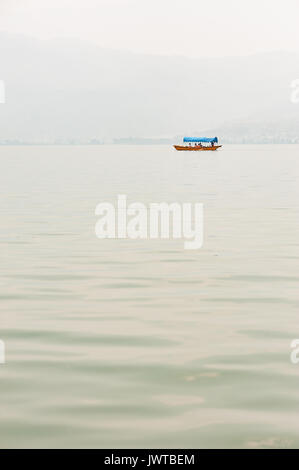 Small boat on a lake in the haze with mountains in the background - Stock Photo