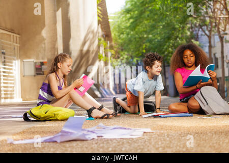 Group of kids reading books and textbooks on the ground near the school - Stock Photo