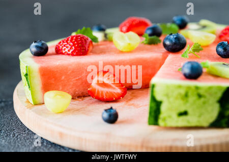 Cut in watermelon pizza with fruits: strawberry, kiwi, grapes, blueberry and mint, on wooden board. Dark background, - Stock Photo