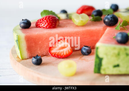 Cut in watermelon pizza with fruits: strawberry, kiwi, grapes, blueberry and mint, on wooden board. White background - Stock Photo