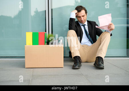 Fired businessman reading the notice of job termination outside a financial district building - Stock Photo
