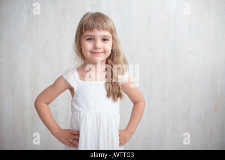 Portrait of pretty little girl in white dress , looking at camera and smiling, standing against gray background. - Stock Photo