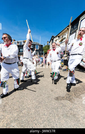 Traditional English folk dancers, Woodchurch Morris group, dancing on seafront harbour jetty during Broadstairs - Stock Photo