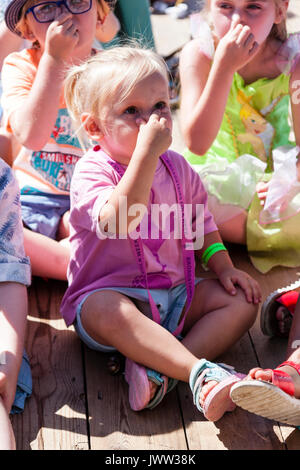 Young blonde girl child, 3-4 years old, sitting on wooden decking with other children as part of audience watching - Stock Photo