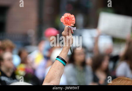 Chicago, USA. 13th Aug, 2017. A participant raises a flower during in an evening vigil at Federal Plaza in Chicago, - Stock Photo