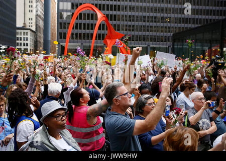 Chicago, USA. 13th Aug, 2017. People raise flowers during an evening vigil at Federal Plaza in Chicago, the United - Stock Photo