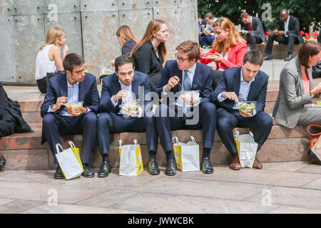 London, UK. 14th August 2017. City workers in the enjoy their lunch in the sunshine in Canary Wharf financial district - Stock Photo