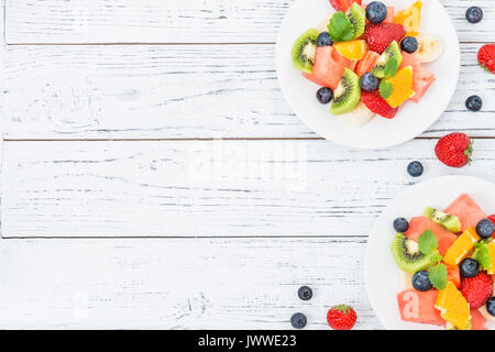 Healthy fresh fruit salad on white plate on wooden table. Top view, copy space. Delicious summer meal: strawberries, - Stock Photo