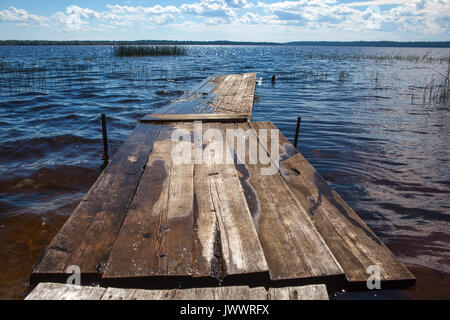 Close up of old, wooden jetty in the autumn fog. - Stock Photo