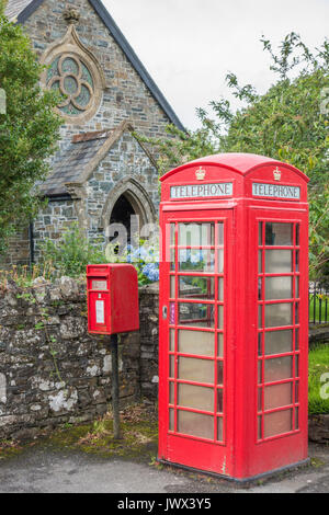 A traditional red Royal Mail postbox alongside an iconic red telephone kiosk, outside the old church, Lydford, near - Stock Photo