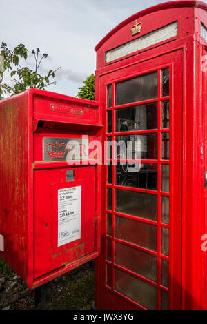 A traditional red Royal Mail postbox alongside an iconic red telephone kiosk, Lydford village, near Okehampton, - Stock Photo