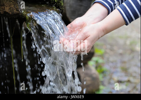 Water pouring in woman hand on nature background - Stock Photo