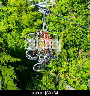 Mountain Bikes Being Transported by Chairlift up to Whistler Mountain for Riding Down to Whistler Village with Pine - Stock Photo