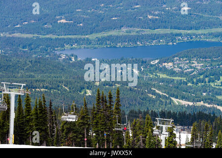 An Express Chairlift at Whistler Ski Resort from The Roundhouse Terrace Area with Whistler Town and Alta Lake British - Stock Photo