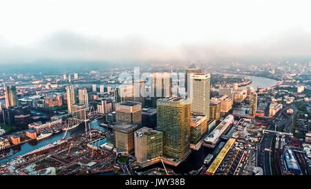 Aerial Image Photo of London City Financial District Skyscrapers in Canary Wharf Helicopter Flight View with Sunrise - Stock Photo