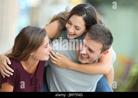 Three happy friends meeting and joking together on the street - Stock Photo