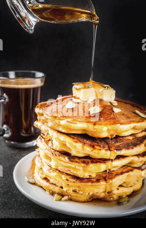 Autumnal traditional food. Stack of pumpkin pancakes with butter, pumpkin seeds and maple syrup. With a cup of coffee. - Stock Photo