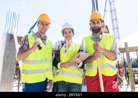 Portrait of confident colleagues posing during work break on construction site - Stock Photo