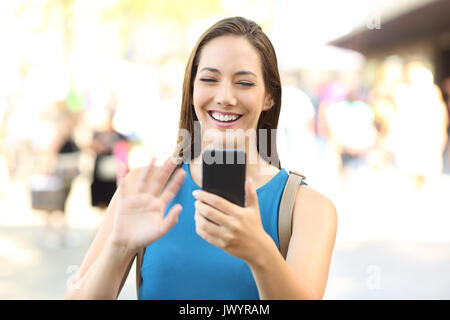 Happy lady greeting during a video call with a smart phone on the street - Stock Photo