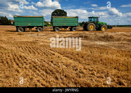 green tractor driving through wheat field - Stock Photo