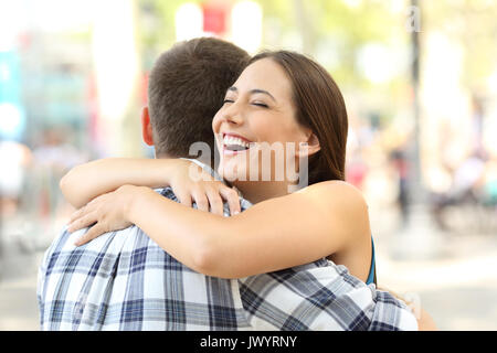 Happy couple or friends hugging after encounter on the street - Stock Photo